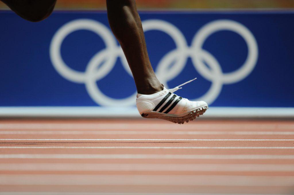JO Beijing 2008, Athlétisme - Les anneaux olympiques au bord de la piste et la jambe d'un athlète pendant la course.